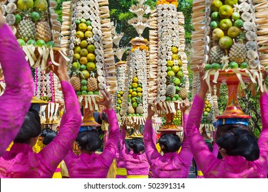Procession of beautiful Balinese women in traditional costumes - sarong, carry offering on heads for Hindu ceremony. Arts festival, culture of Bali island and Indonesia people. Asian travel background