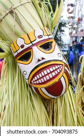 Procession on harvest festival Onam celebration. Men dressed in costume of young coconut leaves performing tribal mask dance in Thrippunithura Kerala, South India.