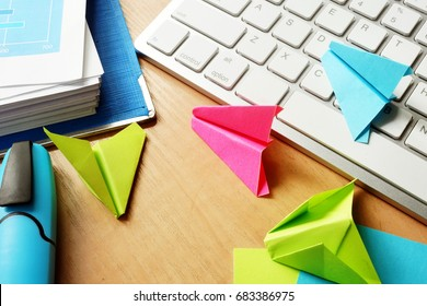 Procrastination concept. Colorful paper planes on a office table.