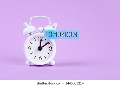 Procrastination, delay and urgency concept. White alarm clock with a sticky note with text tomorrow