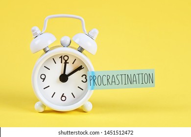 Procrastination, delay and urgency concept. White alarm clock with text procrastination.