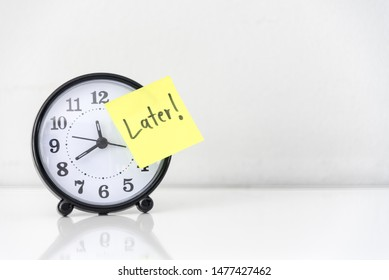 Procrastination delay and urgency concept with word later on yellow sticky paper over white alarm clock, bad time management.
