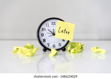 Procrastination delay and urgency concept with word later on sticky paper over white alarm clock and crumpled paper ball, bad time management.