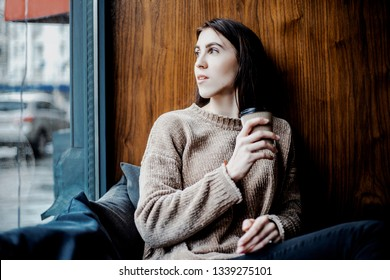Procrastination, depression, sadness. Beautiful pretty woman with serious face drinking coffee near window in cafe near her home. Sad mood, inspiration mood. Waiting for some news or for someone.
