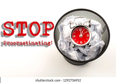 Procrastination is the enemy of productivity and stop wasting time concept with a clock in a black waste basket next to crumpled paper isolated on white background with Stop procrastinating text