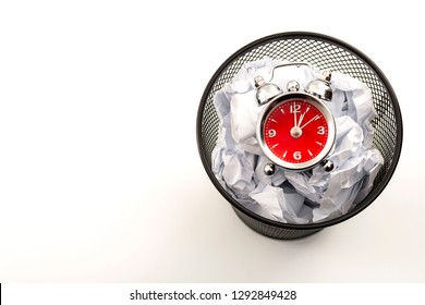 Procrastination is the enemy of productivity and stop wasting time concept theme with a clock in a black waste basket or rubbish bin next to crumpled paper isolated on white background with copy space