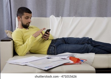 procrastination. A man lying on the couch and looking at the phone. He does not want to work.