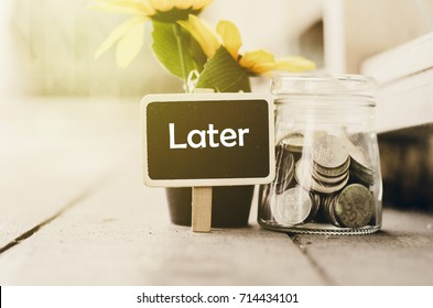 procrastination and urgency concept with word Later on wooden signage, artificial plant and coin in jar. wooden background with light effect