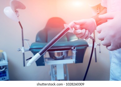 Proctologist holding an anoscope against a proctological chair. In the hospital