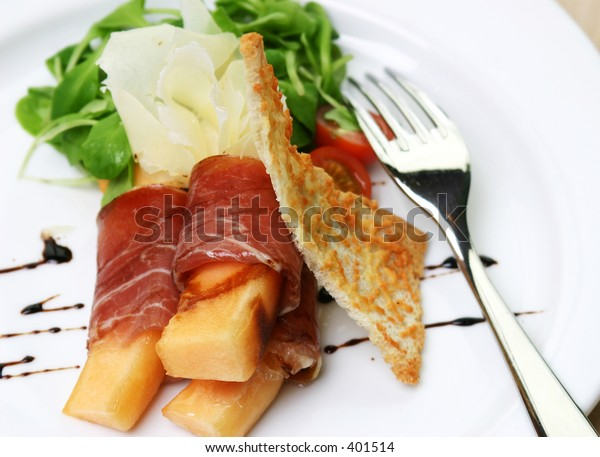 Procuitto ham rolled around fresh melon.  Drizzled with balsamic vinagrette and focaccia bread. Shallow DOF.