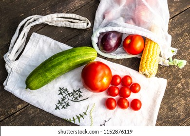 Produce in zero waste reusable shopping bag on wooden natural surface.