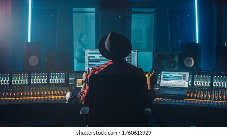 Producer, Audio Engineer Uses Control Desk for Recording New Album Track in Music Record Studio, in the Soundproof Room Musician, Artist, Performer Sings a Song from New Album. Back View