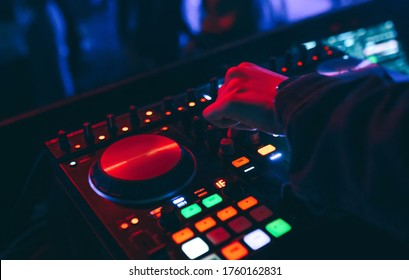 producer  DJ mixer in a nightclub with glowing plays musical rave Dubstep Electronic Trance composition with modern midi controller device in nightclub Live.Musical production process for artists.