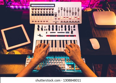 producer hands arranging and mixing music in home studio
