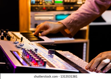 producer hands playing midi keyboard synthesizer for recording in sound studio, music production concept