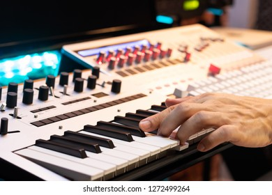 producer hands playing on midi keyboard synthesizer for recording in post production studio