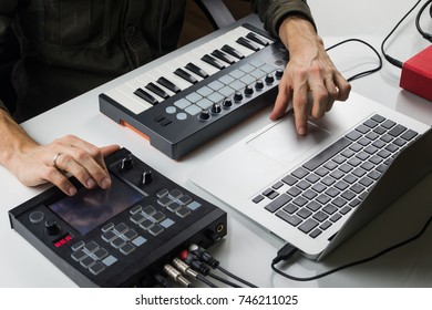 Producing electronic music on laptop with portable midi keyboard and electronic effect processors. Man hands controlling or mixing electronic music track on computer with help of modern devices