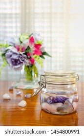 Producing healing gem essence at home on a wooden table. Amethyst, rose quartz and blue lace agate are put into a glass jar with purified water. It will take on the vibrational frequency of the stones