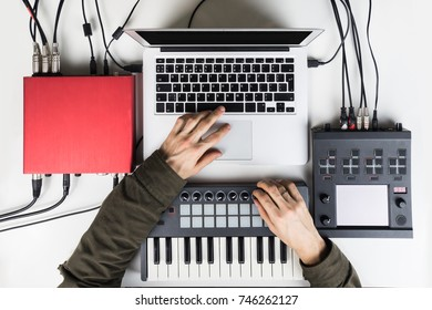 Producing and mixing modern style beats music, beat making and arranging audio content with software controllers and digital effects processors. Recording electronic music track in home studio