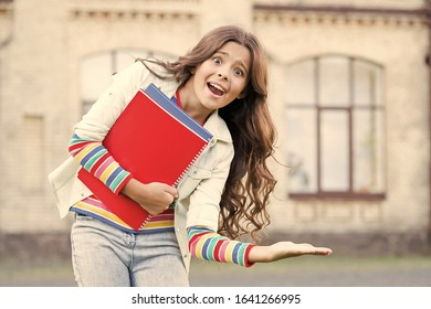 Product advertising. Happy small school age child presenting your product. Little girl with books smiling and presenting product or service. You can never go wrong with this product.