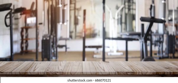 Product display montage Concept. Empty wood table space platform and fitness gym background.