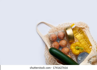 Product goods zucchini, yellow pepper, chicken eggs, canned food, sunflower oil in string bag. Fresh vegetables in the bag, top view flatlay photo on white background. The concept of healthy diet