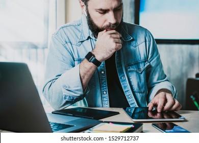 オフィスの職場で製品マネージャが多忙で、タブレットとノートパソコンでデータを学習し、革新的なソリューションを提供。デスク上のガジェットの画面に触れるアプリのデジタル開発者テスト作業。Man Learning Appの機能
