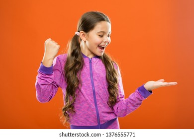 Product presentation. Kid happy face show something on open palm copy space. Girl demonstrate product. Advertisement and commercial concept. Promoting product for kids. Launching product for children.