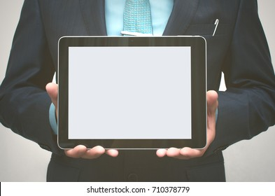Product presentation. Promotion. Business man holding in hands tablet computer with blank screen, close up.