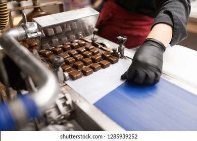 production, candy shop and people concept - confectioner making candies by chocolate coating machine at confectionery