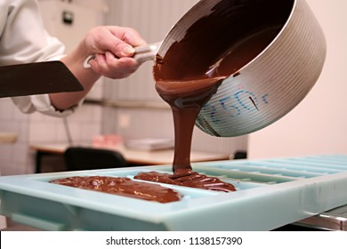 Production of chocolate, pouring melted chocolate mass into molds, chocolate factory