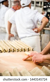 The production of French baguettes is a bakers art. You need to knead the dough properly to get an airy crispy baguette. A professional baker by hand expertly prepares the dough for baking baguettes