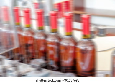 Production of industrial conveyor belt in the winery with glass bottles in the process of work and movement. Motion blur. Not without a sharp focus background for an industrial design