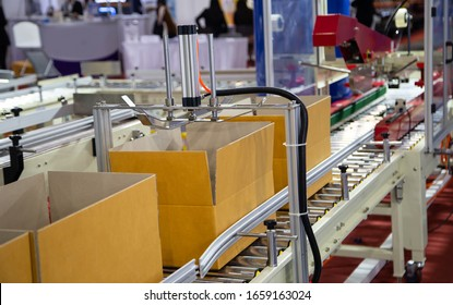 Production line of automated cardboard packing and tape sealing machine. Industrial manufacturing