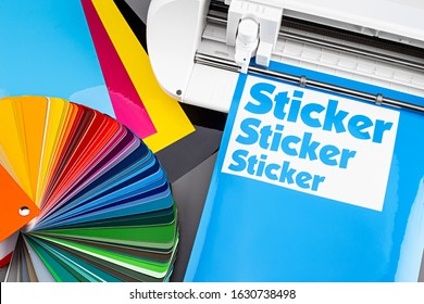 production making sticker with plotter cutting machine on CMYK cyan blue colored vinyl fim with color fan. guide. Advertising Industry diy design concept background.