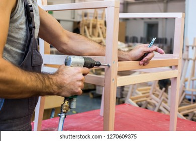 Production, manufacture and industry concept - assembler with electric screwdriver making furniture