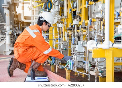 Production operator adjust flow rate of corrosion inhibitor pump as panel man command by radio and record data to logbook, offshore oil and gas activity at wellhead remote platform.