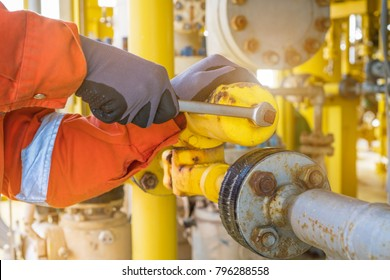 The production operator adjusting pressure regulator of instrument gas supply system, offshore oil rig worker operating on control system at oil and gas wellhead remote platform.