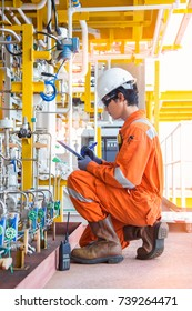 Production operator log record pressure and flow reading value in log book to monitor chemical injection pump performance at oil and gas wellhead remote platform.