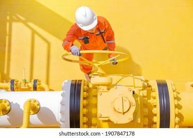 Production operator opening ball valve on offshore oil and gas production platform.