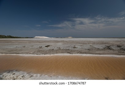 Production of pink and white salt in the Camargue, France, summer 2018. White salt mountain, clear blue sky.