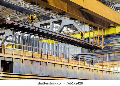 Production process of galvanized steel metal products. Lifting of metal products by overhead crane from hot dip galvanizing bath.