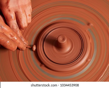 production process of pottery. Forming the clay cover of the kettle on the potter's wheel.
