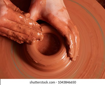 production process of pottery. Forming a clay mug on a potter's wheel.