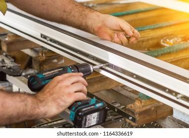Production of pvc windows, a man screws a screwdriver into a pvc window, close-up, windows pvc