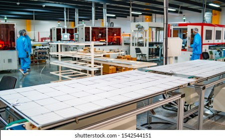 production of solar panels, man working in factory. Closeup of special machinery at solar production panels factory. Industrial technic at plant. Modern green energy production.