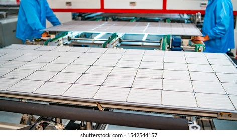 production of solar panels, men working in factory. Closeup of heavy machinery at solar production panels factory. Industrial technic at plant. Green energy concept.