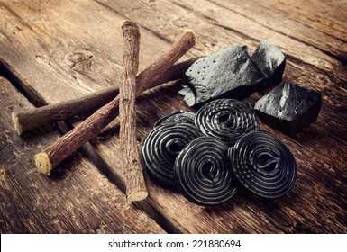 Production steps of licorice, roots, pure blocks and candy on wooden table