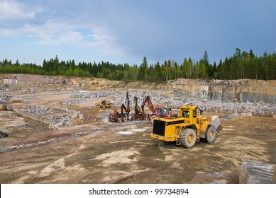 Production of stone in granite quarry. Mining machines
