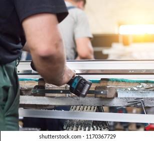 Production windows pvc, man screwed screwdriver hinged defense on the sash pvc frame, close-up, work